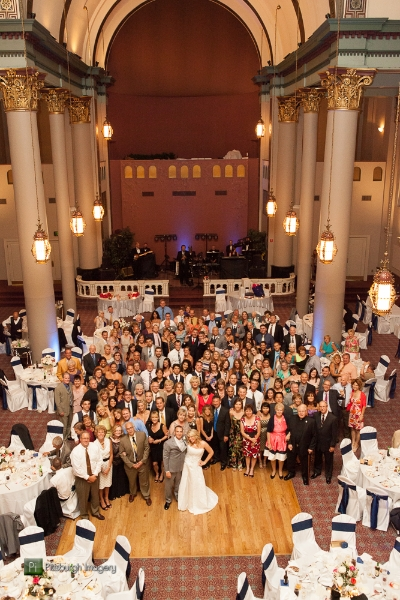 Bride and groom pose with their guests at a Grand Hall at the Priory, Pittsburgh wedding reception.