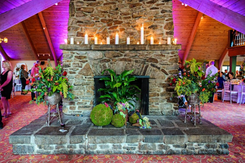 Peek n Peak Wedding Reception Venue with Large Stone Fireplace, Lush Plants, and Romantic Candles