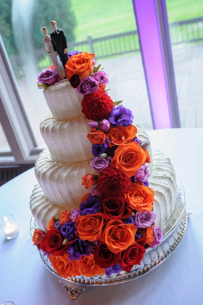Peek n Peak Striped Wedding Cake with Orange and Purple Flower Detailing and Tealight Candles