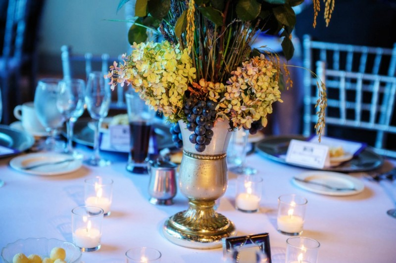 Peek n Peak Wedding Reception Table Centerpiece with Grapes and Flowers in Silver Vase with Tealight Candles