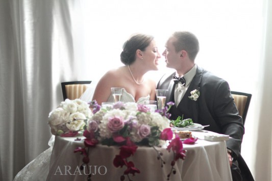 Renaissance Hotel Pittsburgh Wedding - Newlyweds Sit At Table Brimming with Flowers