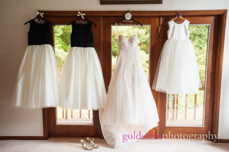 Bride Gowns and Bridesmaid Dresses Hanging on Door at House before Wedding